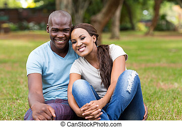 african american couple sitting in the park