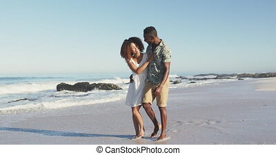 Front view of an African American couple enjoying time in the sun on a tropical beach, embracing, walking and looking at each other, in slow motion