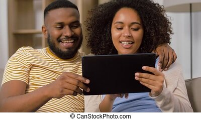 african american couple with tablet pc at home