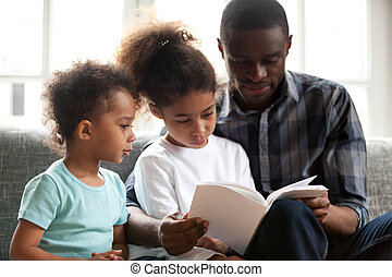 African American dad reading book to small kids
