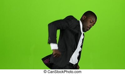 African american dancing jumps up and turns around. Green screen. Slow motion