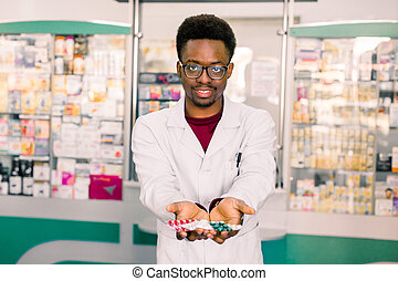 African-american Doctor pharmacist man holding tablets pills blisters in the hands.