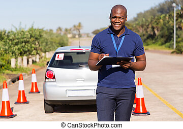 african american driving instructor writing on clipboard -...
