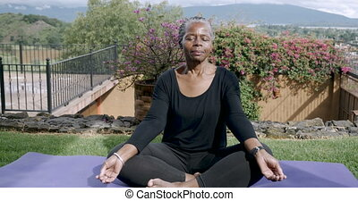 African American elderly woman sitting quietly mediating with her legs crossed