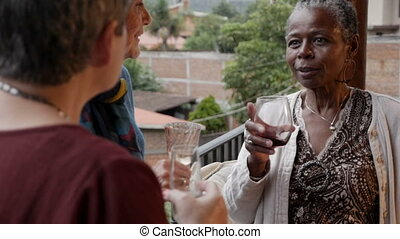 African American elderly woman talking and drinking wine...