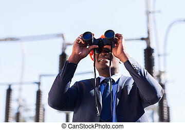 african american electrical manager using binoculars