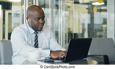African American entrepreneur in formal clothes working on laptop while listening to music with earbuds in his ears in a modern cafe