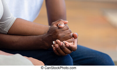 African american family couple holding hands, close up view