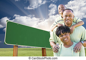 African American Family in Front of Blank Green Road Sign