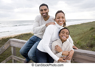 African-American family smiling and hugging at beach