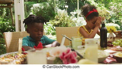 African American family spending time in garden together, sitting at a dinner table, saying a prayer with their eyes closed, in slow motion.