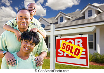 African American Family with Sold For Sale Sign and House -...