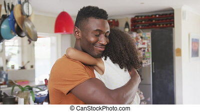 Front view of an African American man and his mixed race daughter enjoying time at home together, a man is holding his daughter up, embracing and smiling, in slow motion