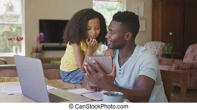 African american father and daughter looking a digital tablet