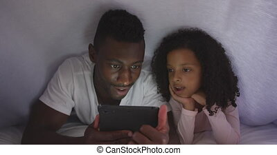 Front view of an African American man and his mixed race daughter enjoying time at home together, lying on a bed under a duvet, using a digital tablet, laughing, in slow motion