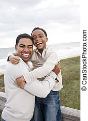 African-American father and son laughing at beach