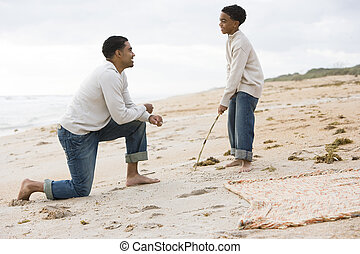 African-American father and son playing on beach -...