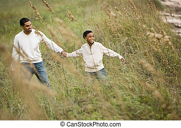 African-American father and son walking through grass at...