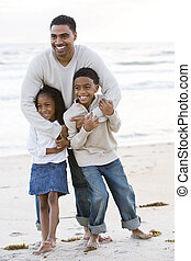 African-American father and two children on beach - Happy ...