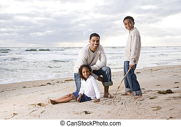 African-American father and two children on beach