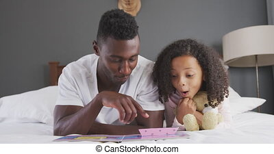 African american father reading a story to his daughter in ...