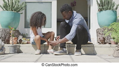 African american father tying his daughter shoes - Side view...