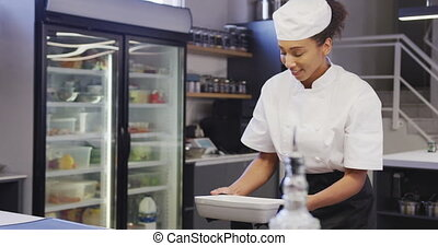 A professional African American female chef wearing chefs whites in a restaurant kitchen, taking food out of an oven in slow motion