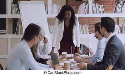 Serious young african american female company boss holding meeting with diverse corporate workers. Focused mixed race leader talking with teammates, discussing project ideas or growth strategy.