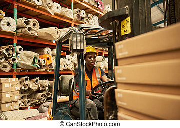 African American female forklift driver working in a textile warehouse