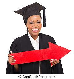 african american female graduate holding direction arrow