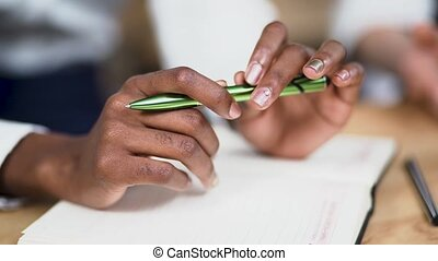 African-American female hands are holding pen. Closeup -...