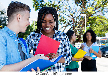 African american female student learning with caucasian male student