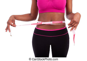 African American Fitness woman measuring her belly