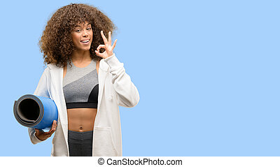 African american fitness woman training doing ok sign with fingers, excellent symbol