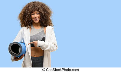 African american fitness woman training very happy pointing with hand and finger