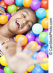 African American Girl Child Playing in Colored Balls