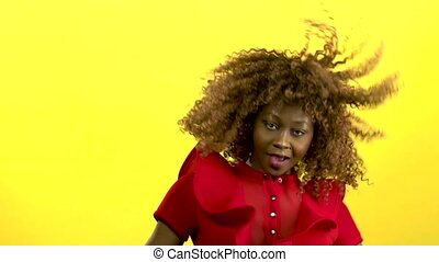 African american girl jumping and having fun with music. Yellow background. Slow motion