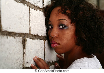 African American Girl Lean Her Face On Brick Wall - african...