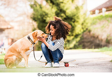 African american girl outdoors on skateboard with her dog...