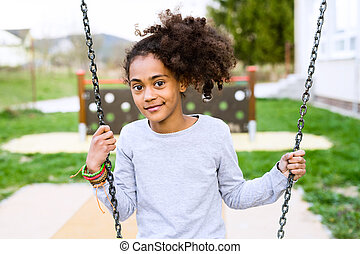African american girl outdoors sitting on swing.