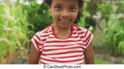 African American girl showing potatoes at the camera - Front...
