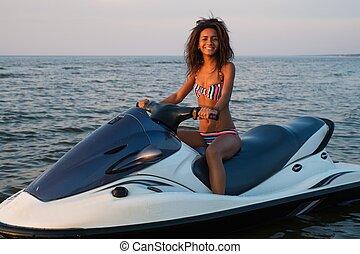 African-american girl sitting on a jet ski