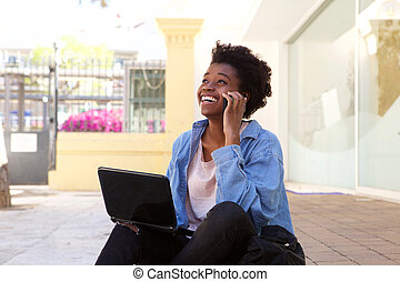 African american girl sitting on sidewalk and talking on mobile phone with laptop