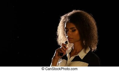 African american girl smokes an electronic cigarette in an empty room. Black background