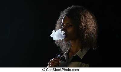 African american girl smokes an electronic cigarette in an empty room. Black background. Slow motion