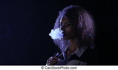 African american girl smokes an vaping in an empty room....