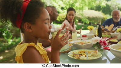 African American girl spending time in garden, sitting at a dinner table with her family, drinking lemonade and smiling, in slow motion.