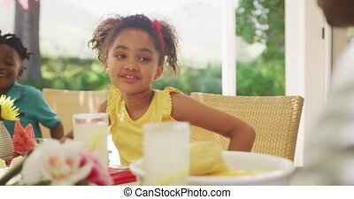 African American girl spending time in garden, sitting at a dinner table with her family, listening to her father talking, in slow motion.