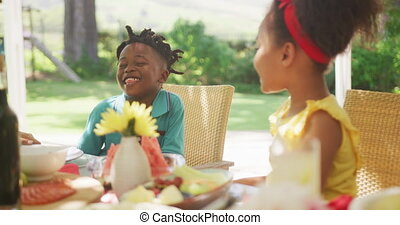African American girl spending time in garden, sitting at a dinner table with her family, whispering to her brother ear and laughing, in slow motion.