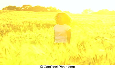 African American girl teenager walking in wheat field at sunset
